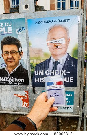 STRASBOURG FRANCE - APR 23 2017: French voter registration card held by male hand in front of official campaign poster of Francois Asselineau candidate for the 2017 French presidential elections posted outside a polling station