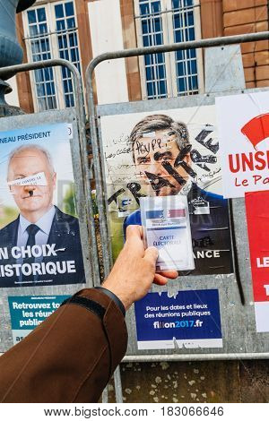 STRASBOURG FRANCE - APR 23 2017: French voter registration card held by male hand in front of official campaign poster of Francois Fillon candidate for the 2017 French presidential elections posted outside a polling station