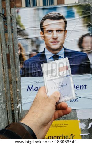 STRASBOURG FRANCE - APR 23 2017: French voter registration card held by male hand in front of official campaign poster of Emmanuel Macron candidate for the 2017 French presidential elections posted outside a polling station