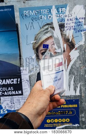 STRASBOURG FRANCE - APR 23 2017: French voter registration card held by male hand in front of official campaign poster of Marine Le Pen candidate for the 2017 French presidential elections posted outside a polling station