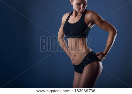 Young athletic woman in sportswear poses for the camera against a dark blue background
