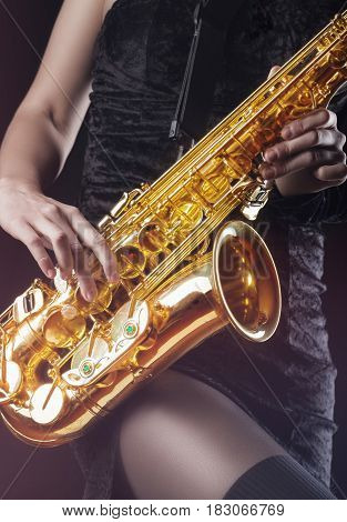 Saxophonist. Closeup of a woman with a sax on a dark background