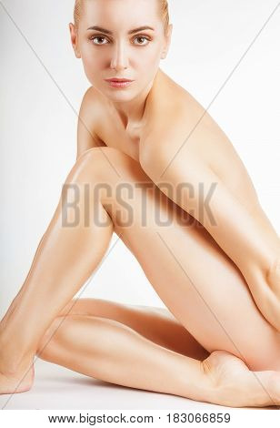 Health and beauty concept. Beautiful young woman looking at camera sitting against white background