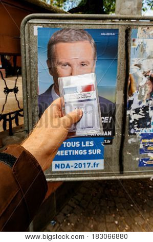 STRASBOURG FRANCE - APR 23 2017: French voter registration card held by male hand in front of official campaign poster of Nicolas Dupont-Aigna candidate for the 2017 French presidential elections posted outside a polling station
