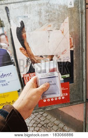 STRASBOURG FRANCE - APR 23 2017: French voter registration card held by male hand in front of official campaign poster of Benoit Hamon candidate for the 2017 French presidential elections posted outside a polling station
