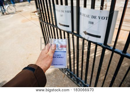 STRASBOURG FRANCE - APR 23 2017: French voter registration card held by male hand in front of Bureau de Vote Voting Section open for the 2017 French presidential elections posted outside a polling station blak and white