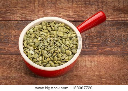 raw, shelled pumpkin seeds in a stoneware cup against rustic barn wood background