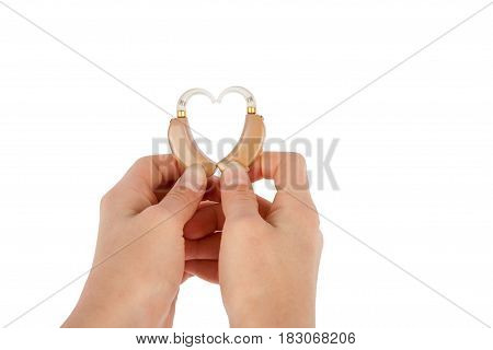 Hands of a woman forming heart shape from hearing aids. Studi shot isolated on white background.