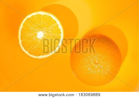 Two oranges on orange background. Art food concept.