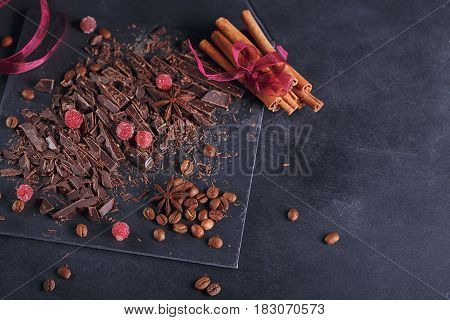 Dark chopping chocolate black roasted coffee beans red berries with spices cinnamon and anise on slate board over black textural background. Top view with space for text.