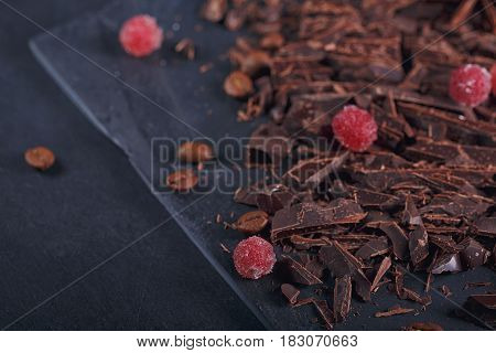 Dark chopping chocolate black roasted coffee beans red berries with spices on slate board over black textural background. Chocolate dessert confectionery and sweets concept