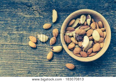 Nuts mix of almonds and Brazil nuts in wooden bowl on old rustic background with place for text. Healthy edible seeds food ingredient on the table. Top view. Copy space.