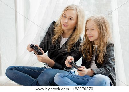 Family games. Mother and daughter play on conlsole together. Lifestyle