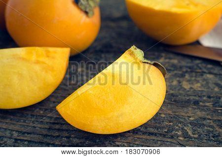 Slice of ripe delicious fresh persimmon kaki fruit on old wooden table.