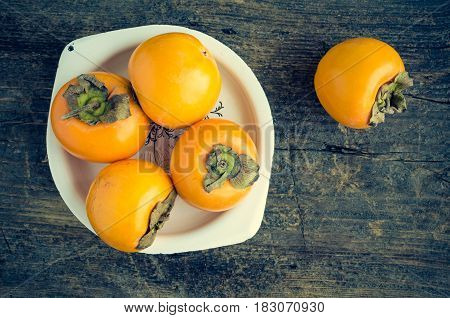 Ripe delicious fresh persimmon kaki fruit in white metal plate on old wooden table with place for text. Top view. Copy space.