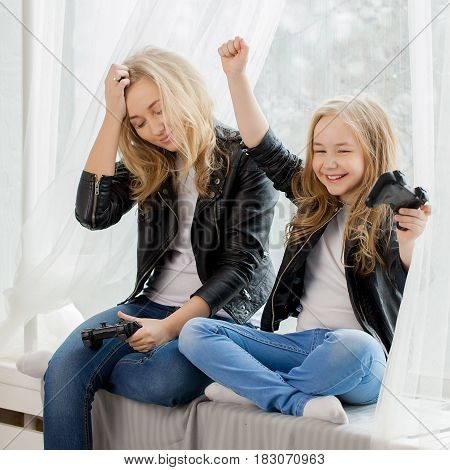 Family games. Mother and daughter play on colsole together