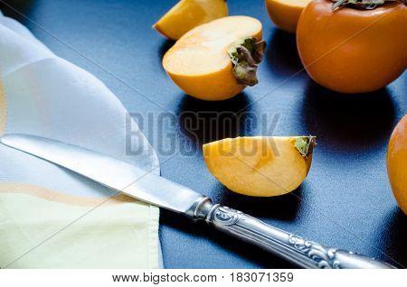 Slice of ripe delicious fresh persimmon kaki fruit with knife and napkin on black background.
