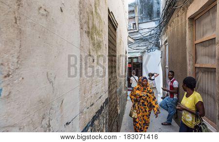Zanzibar, Tanzania - July 14, 2016: Muslim woman walking in Zanzibar, Tanzania in a colorful burka, narrow streets of old town