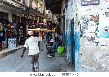 Zanzibar, Tanzania - July 14, 2016: Local market in Tanzania, muslim man selling colorful glasses, old and half-ruined buildings around