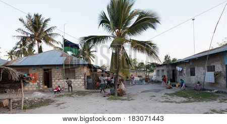 Zanzibar, Tanzania - July 14, 2016: Small village in Zanzibar, palms d a few shacks, children playing outside, women doing chores