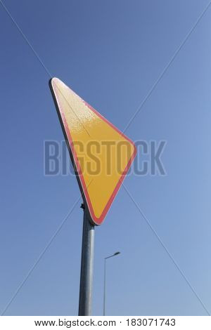 Give way yellow traffic sign.