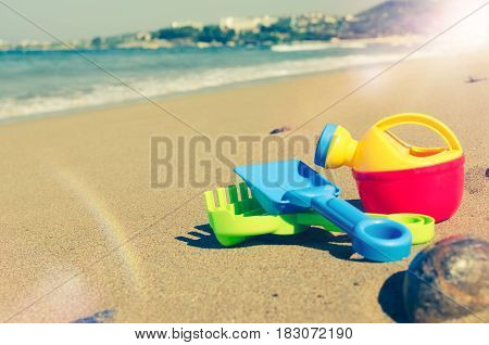 Vacation image of children's beach toys on the sand in beautiful sunny day. Kids summer holidays concept. Copy space.