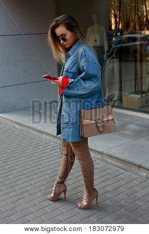 People beauty fashion lifestyle and color concept - Detail of a beautiful young woman with a knee. Street style portrait of a stylish girl with long straight brown hear hear hessian boots.