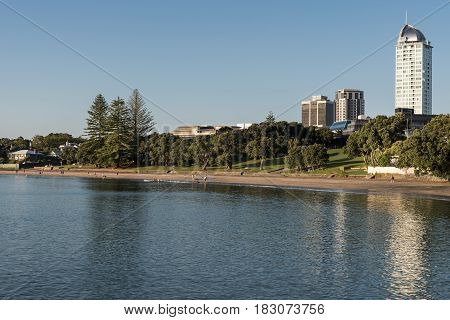 Auckland New Zealand - March 2 2017: South shore of Tapapuna Beach shows park highrise and canoe rowers under blue sky with reflecting sea water.