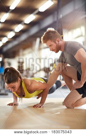 Girl train with trainer help in gym