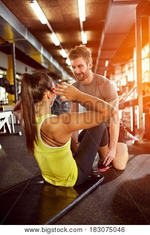 Sportswoman on training with trainer in gym