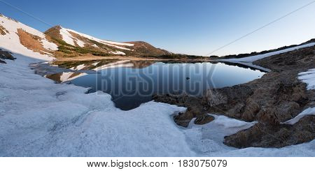 Mountain Lake in the spring. Mountain landscape in the morning. The last snow on the hills. Reflection of the sky in water. Carpathians, Ukraine, Europe