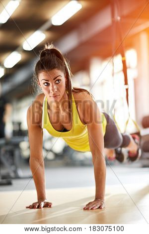 Sportswoman doing pushups in gym