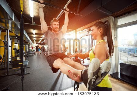 Man with trainer on training in gym on exercise equipment