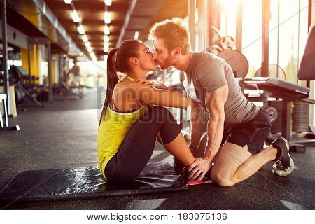 Couple in love kissing while exercise in gym