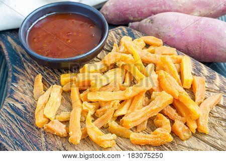 Healthy baked sweet potato fries on wooden board served with spicy sauce horizontal