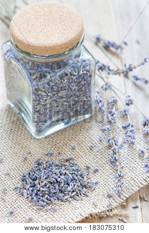 Dry lavender tea in glass jag and on wooden background vertical