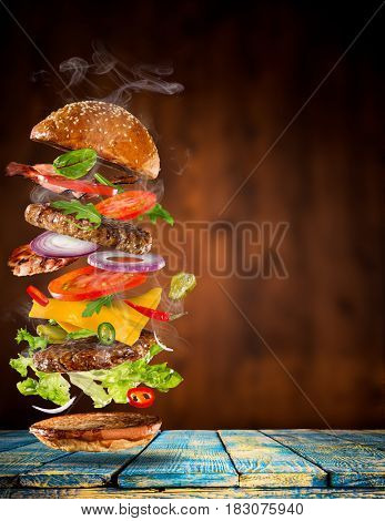 Big tasty home made burger with flying ingredients.