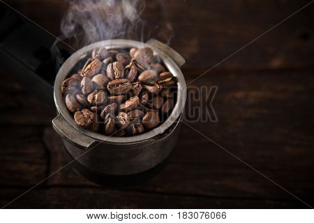 Fresh coffee beans in coffee maker on old wooden table.
