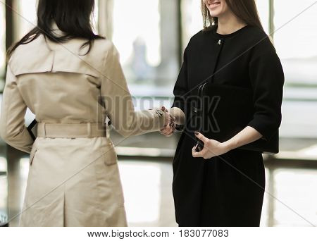 Close-up - the handshake of the company manager and the client in the lobby of the modern office.