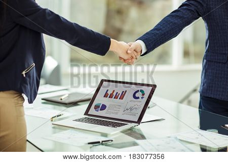 in the foreground is shaking hands with financial partners near the workplace in the modern office