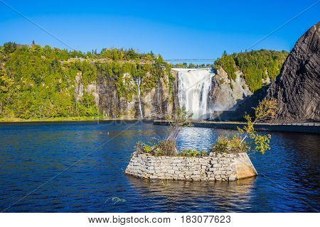 Montmorency Falls Park, in Quebec.  Small picturesque artificial island on the lake. Above the waterfall built bridge for walking. The concept of active and cultural tourism