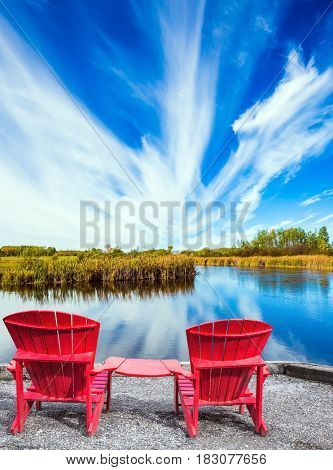 Lovely place to relax. Cirrus clouds are reflected in the Winnipeg River. Two red beach chairs on the riverbank. Old Pinawa Dam Park. The concept of ecological and recreational tourism