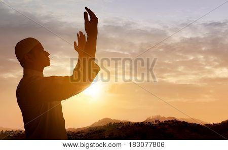 Muslim man praying to God at sunset