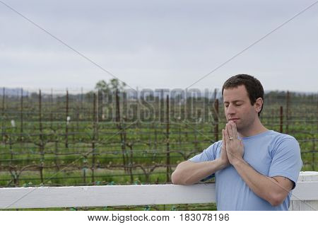 Man praying leaning on a white fence in a vineyard.