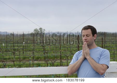 Man praying in front of farmland alone in front of a white fence.