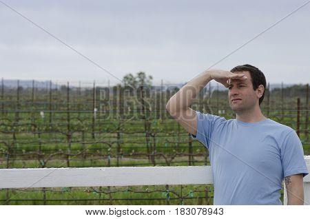 Man with hand on his forehead looking off into the distance with a vineyard behind him.