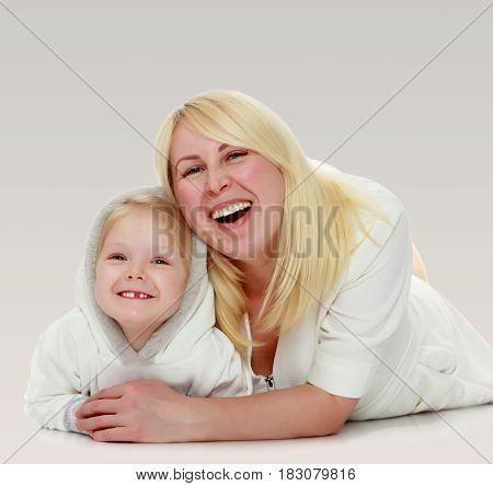 Happy family mother and little daughter lying on the floor and laughing directly into the camera.
