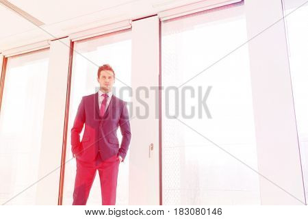 Portrait of confident young businessman standing with hands in pockets against office window