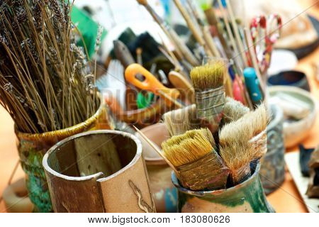Group of brushes and tools n an artist's workshop.