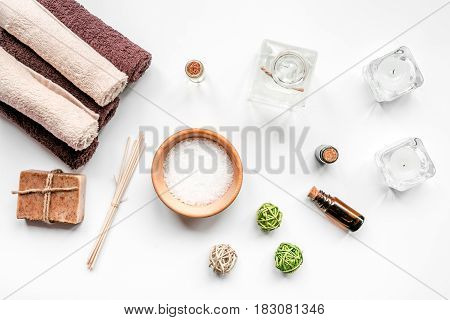 spa cosmetics set with soap, salt, oil on white desk background top view